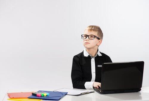 Bilgisayar başında yan tarafa bakan gözlüklü çocuk