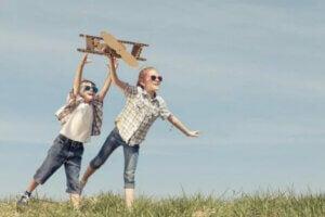 İki çocuk karton uçak uçururken