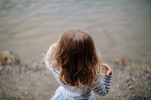 su kenarında duran çocuk