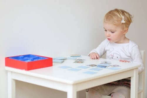 küçük çocuk bir masada oturmuş kartlarla hafıza oyunu oynuyor