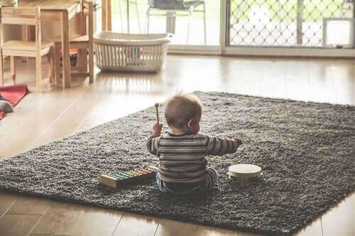 küçük bebek halının üstünde oturmuş müzik aletleriyle oynuyor