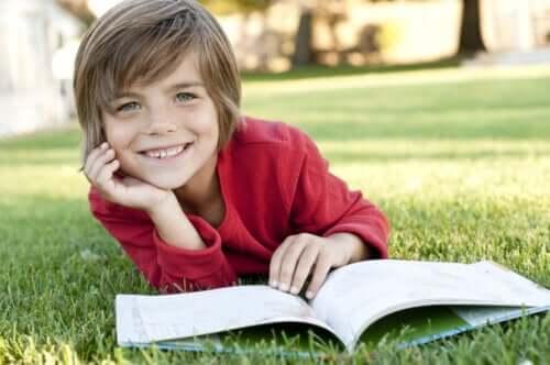 Çimlerin üzerinde kitap okuyan bir çocuk