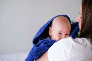 banyo havlusuna sarılı bir bebek ve annesi