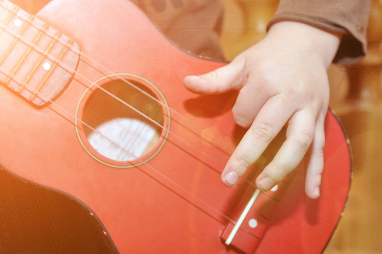 Gitar çalan bir çocuk