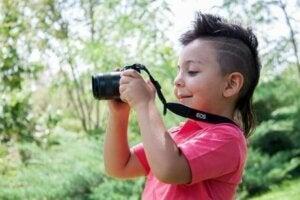 Ormanda kamerasıyla çekim yapan bir çocuk