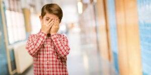 Utangaç çocuk yüzünü kapatıyor