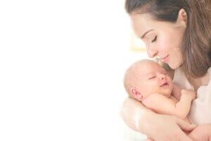 yeni doğan bebeğini kucaklayan anne