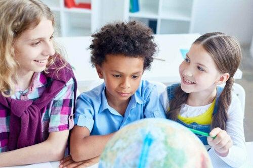 dünya haritasına bakan çocuklar