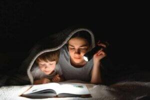 Annesi ile karanlıkta battaniyenin altında kitap okuyan çocuk