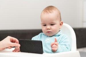 cep telefonuna bakarak eğlenen bir bebek