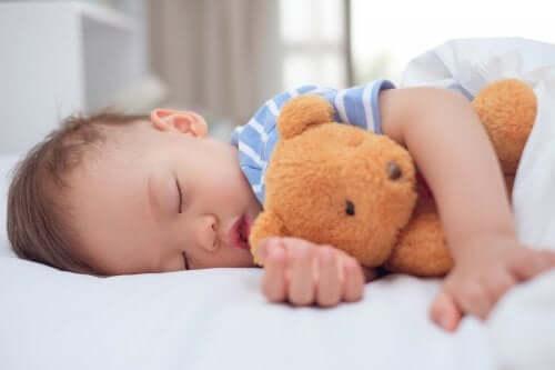 oyuncağa sarılıp uyuyan erkek çocuk
