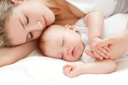 Uyuyan bebeğine sarılmış anne
