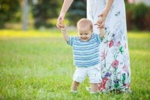 Annesinin yardımı ile yürüyen bebek