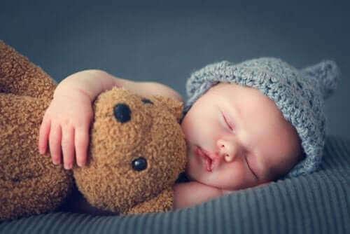 bebekler ilk üç aylık süreçte nasıl uyur: oyuncak ayıya sarılarak uyuyan bebek