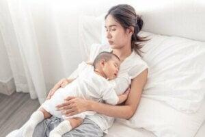 Bir anne ve bebek yatakta birlikte uyuyor.