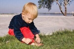 Küçük bir çocuk ayakkabı bağcığını bağlıyor