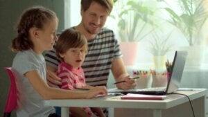 Baba bilgisayarda ders çalışan çocuklarına yardımcı oluyor