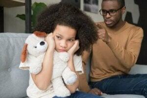 Bir baba kızına kızarken çocuk kulaklarını tıkıyor.