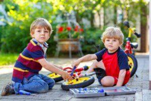 İki çocuk oyuncak bisikletlerini tamir etmeye çalışıyor