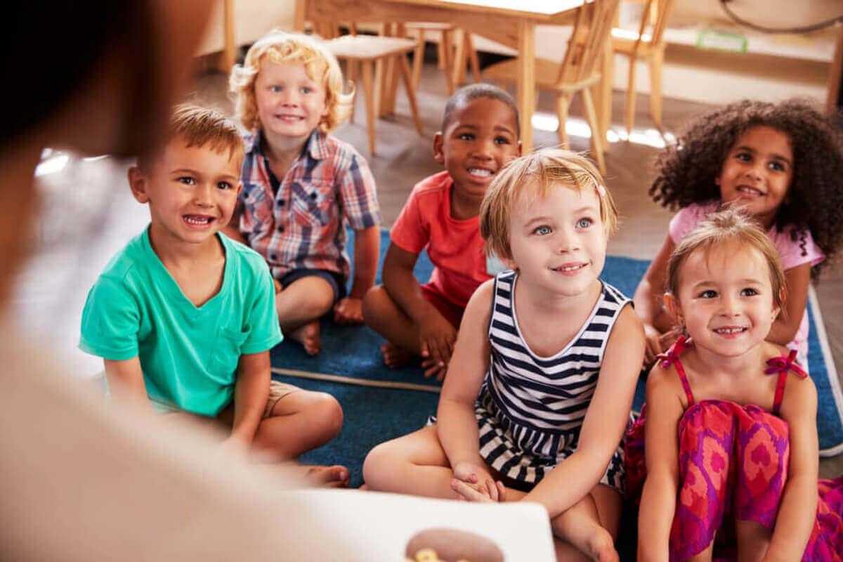 Yerde oturmuş ders dinleyen beş yaş altı çocuklar