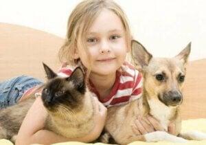 Kedisi ve köpeği ile poz veren kız