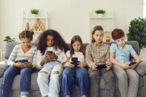 Beş çocuk oturup konuşmadan telefona bakıyorlar