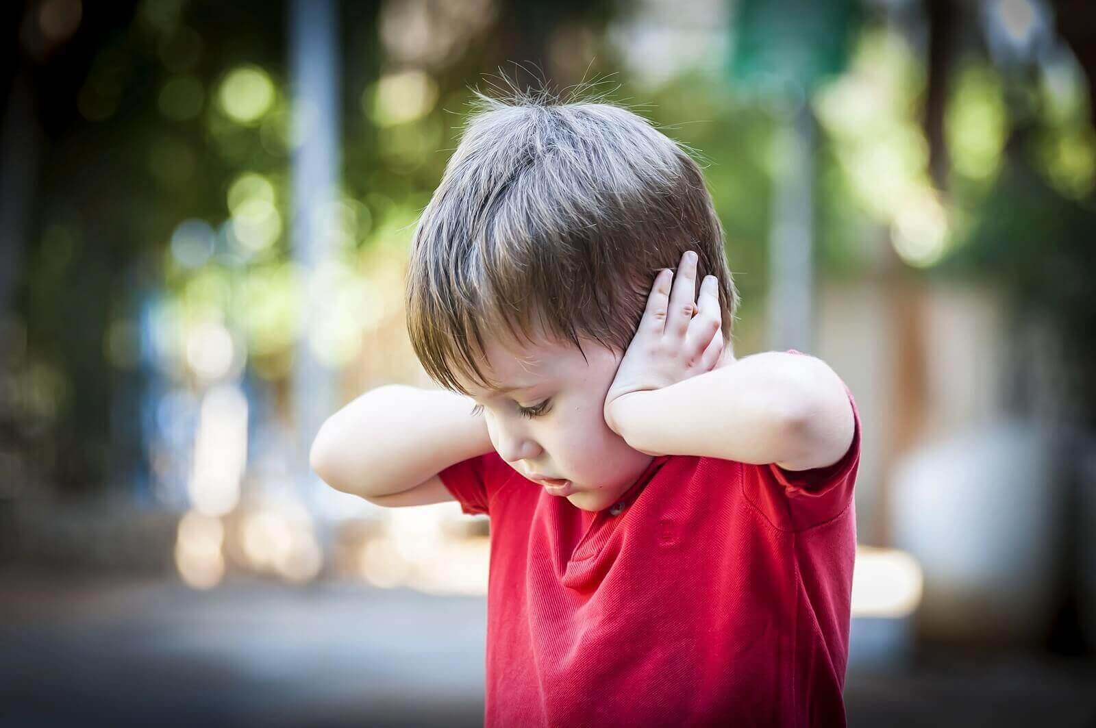 İki eliyle kulaklarını tıkayan erkek çocuk