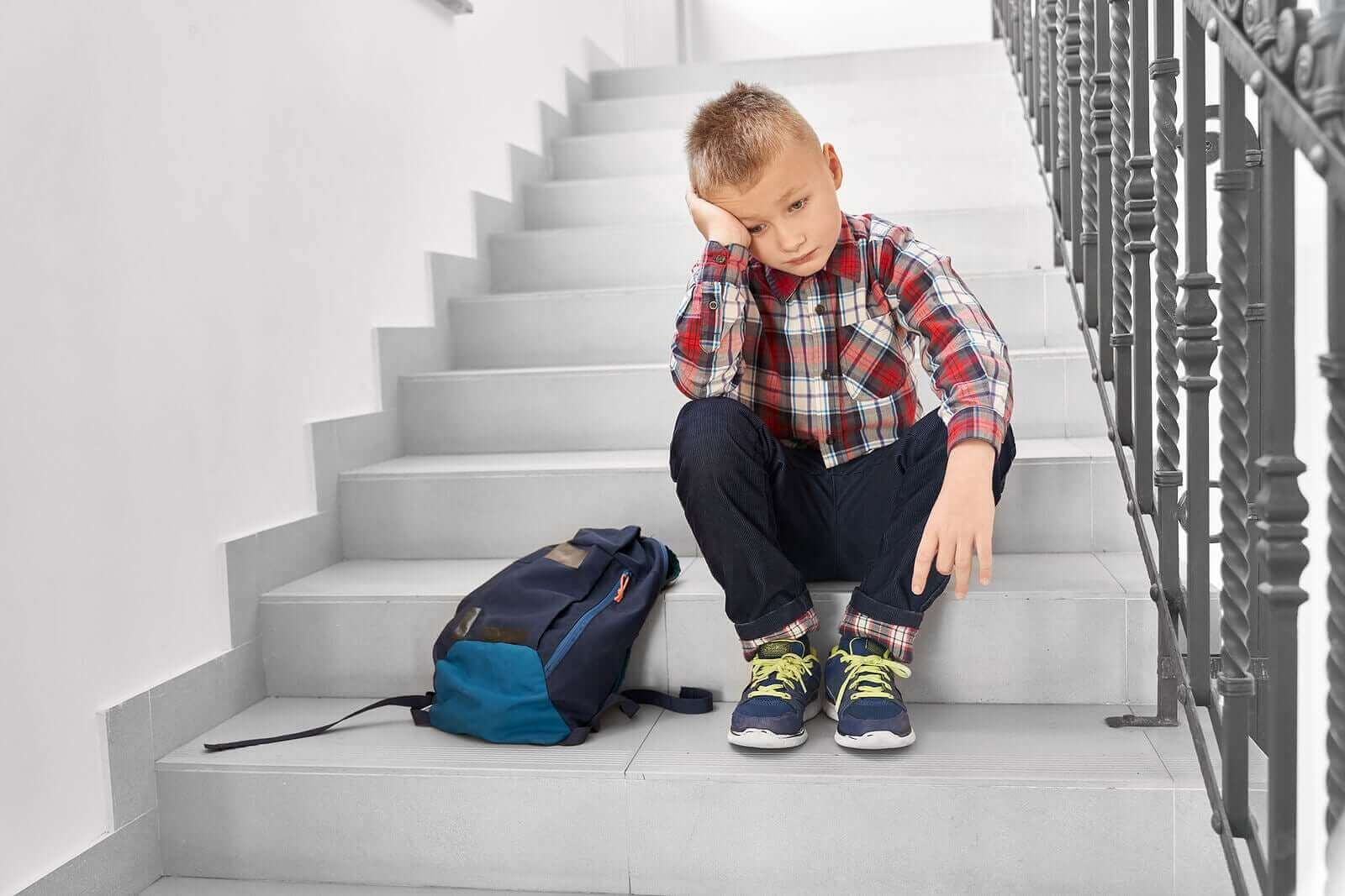 Merdivende yalnız başına oturmuş düşünen çocuk