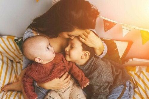 bebeğine ve oğluna sarılan anne