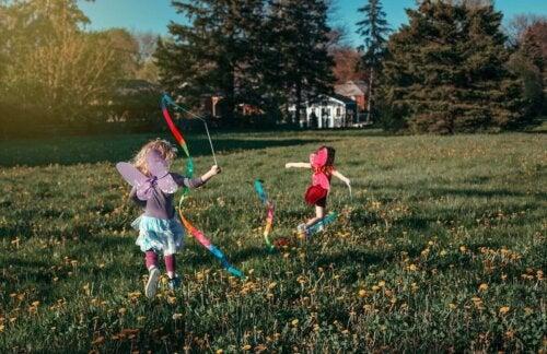 Peri gibi giyinmiş, çimenlerde koşan kız çocukları.