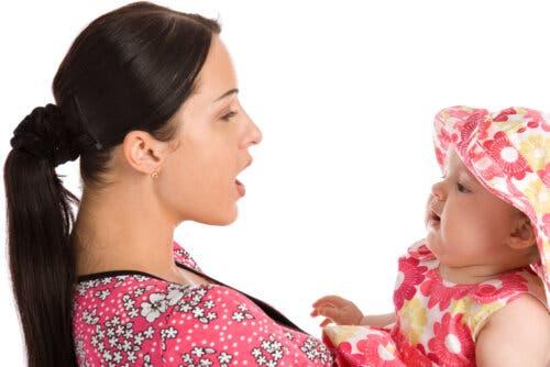 annesinin kucağında şapkalı bebek ve evrimsel dil bilimi