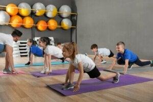 Eğitmen eşliğinde egzersiz yapan çocuklar