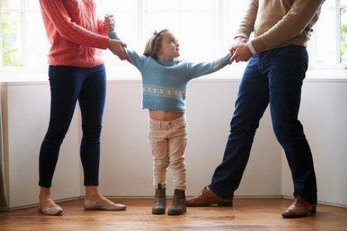 İki kolundan çeken anne babasına bakan küçük kız