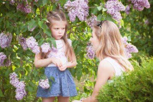 Bahçede çiçekler arasında annesine kızarak bakan kız
