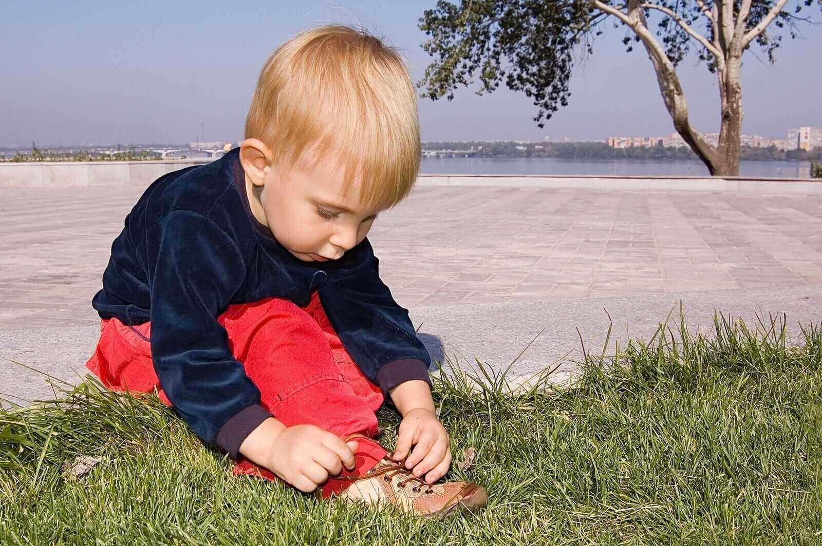 ayakkabısını bağlayan yalnız çocuk