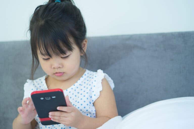 elindeki telefona bakan kız çocuğu