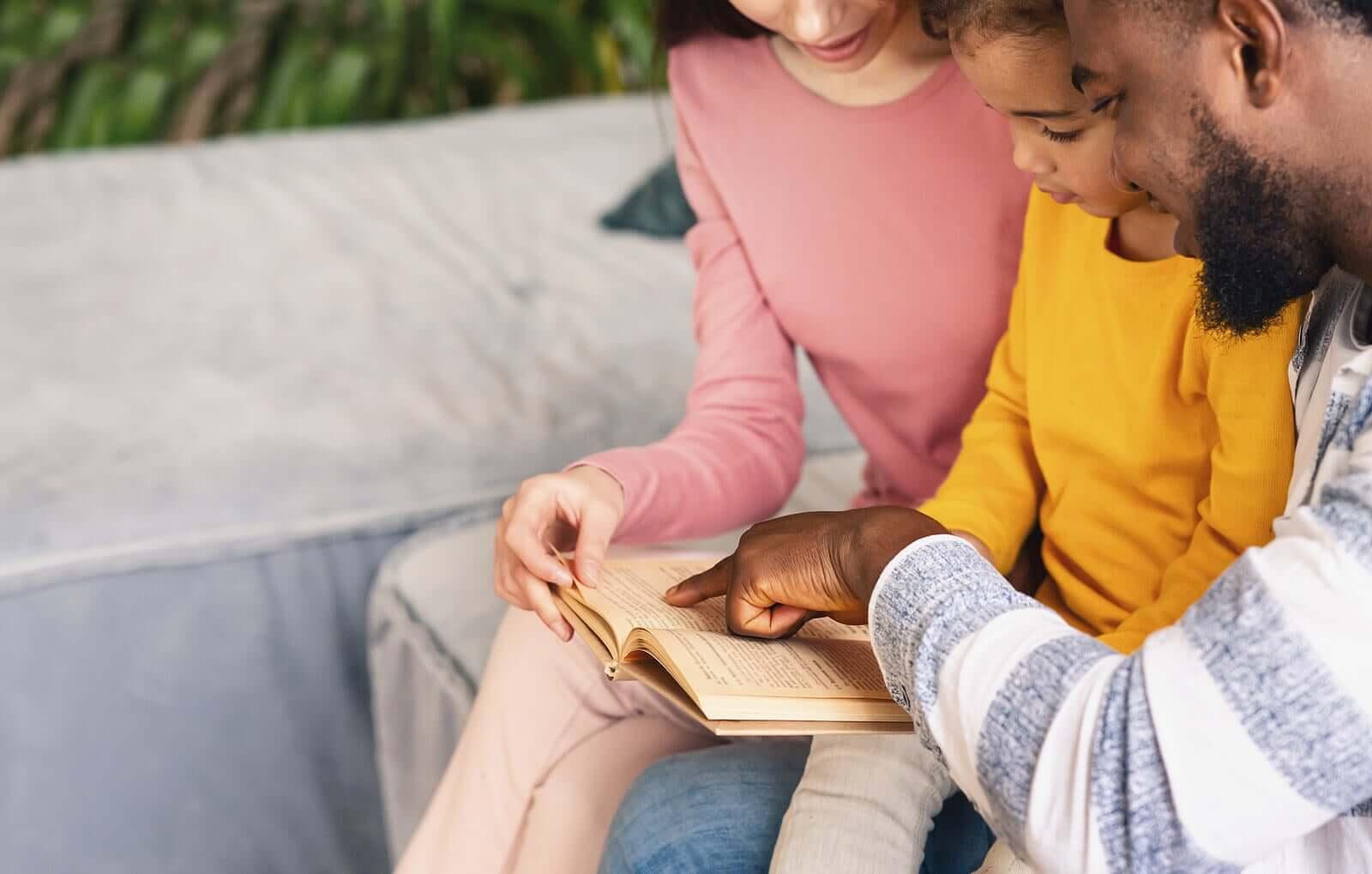 çocukları ile yüksek sesle kitap okuyan anne ve baba