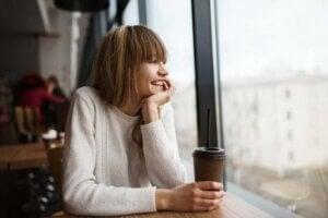 Kahvesini izlerken dışarıyı izleyen genç kız