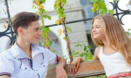 Birbirlerine gülümseyen ergenlik dönemlerindeki iki çocuk.