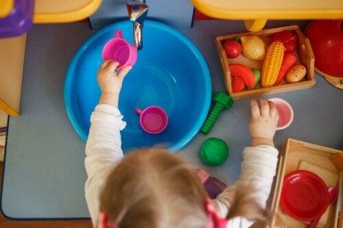 Oyuncak mutfak eşyalarını düzenleyen bir çocuk.