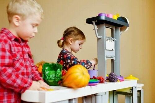 Oyuncak bir mutfakta oynayan iki çocuk.