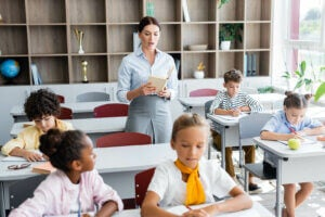 sınıfta çocuklara okuyarak dikte eden bir öğretmen
