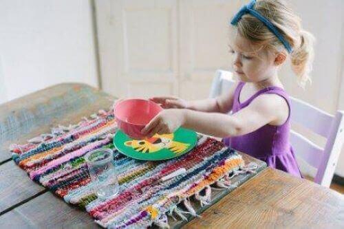 Kendi tabağını masaya koyan kız