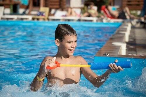 Havuzun içinde su tabancası ile oynayan bir çocuk.