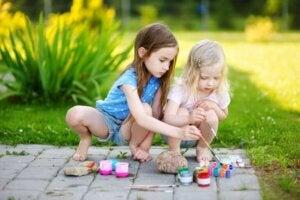İki çocuk bahçede taş boyuyorlar