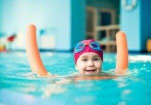 küçük bir çocuk havuzda gülümseyerek yüzüyor