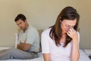 Bir çift yatakta sırtlarını dönmüş oturuyor, kadın ağlıyor