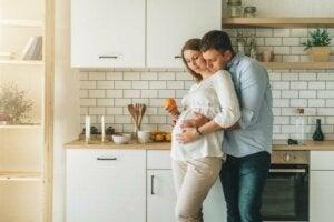 Bir çift mutfakta sarılmışlar, adam hamile kapısının karnını okşuyor