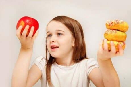 Elinde elma ve kek tutan kız