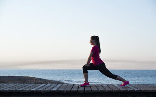 Deniz kenarında spor yapan bir kadın.